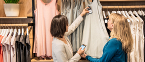 Woman uses a handheld device to scan a dress in a retail store.
