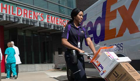 A woman delivering packages in front of a hospital