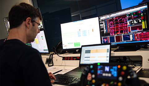 A male developer looking at several screens.