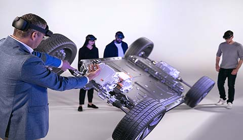 Four people are wearing HoloLenses and they are looking at a holographic car chassis