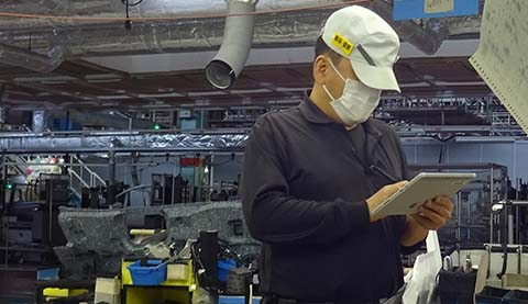 A man is standing in a factory while he is holding a table PC