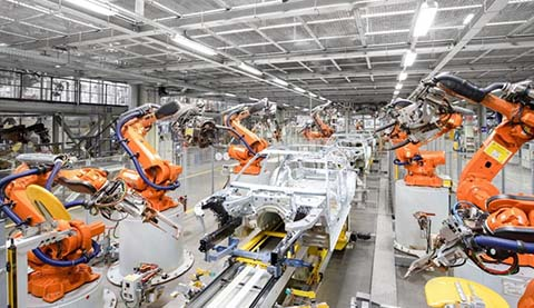 Robots in a factory which are building a car