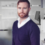 Photo of man in white shirt and blue jumper in office, Hugh Fletcher. He has dark hair and a beard.