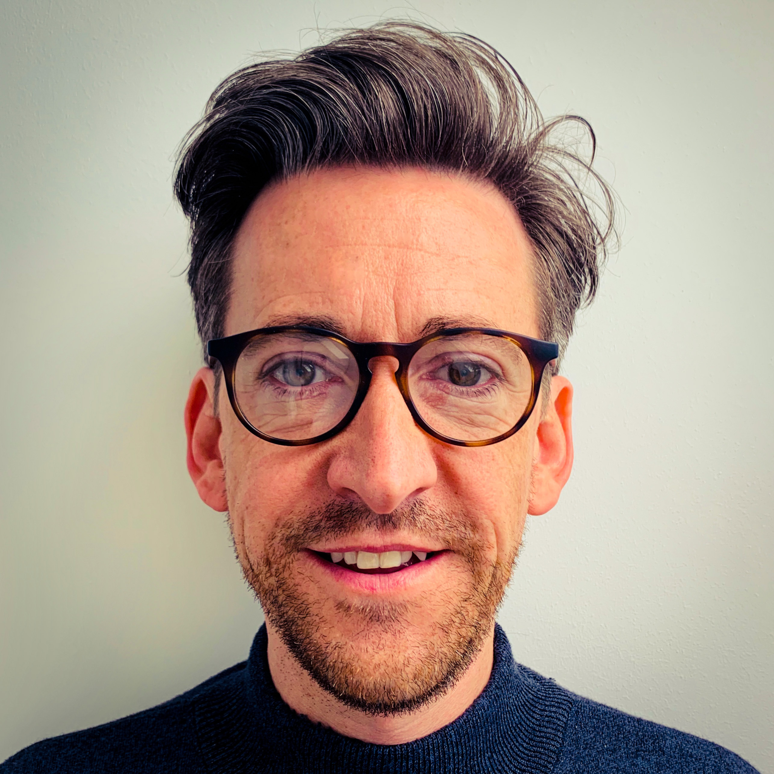 Stuart Almond wearing glasses and smiling at the camera