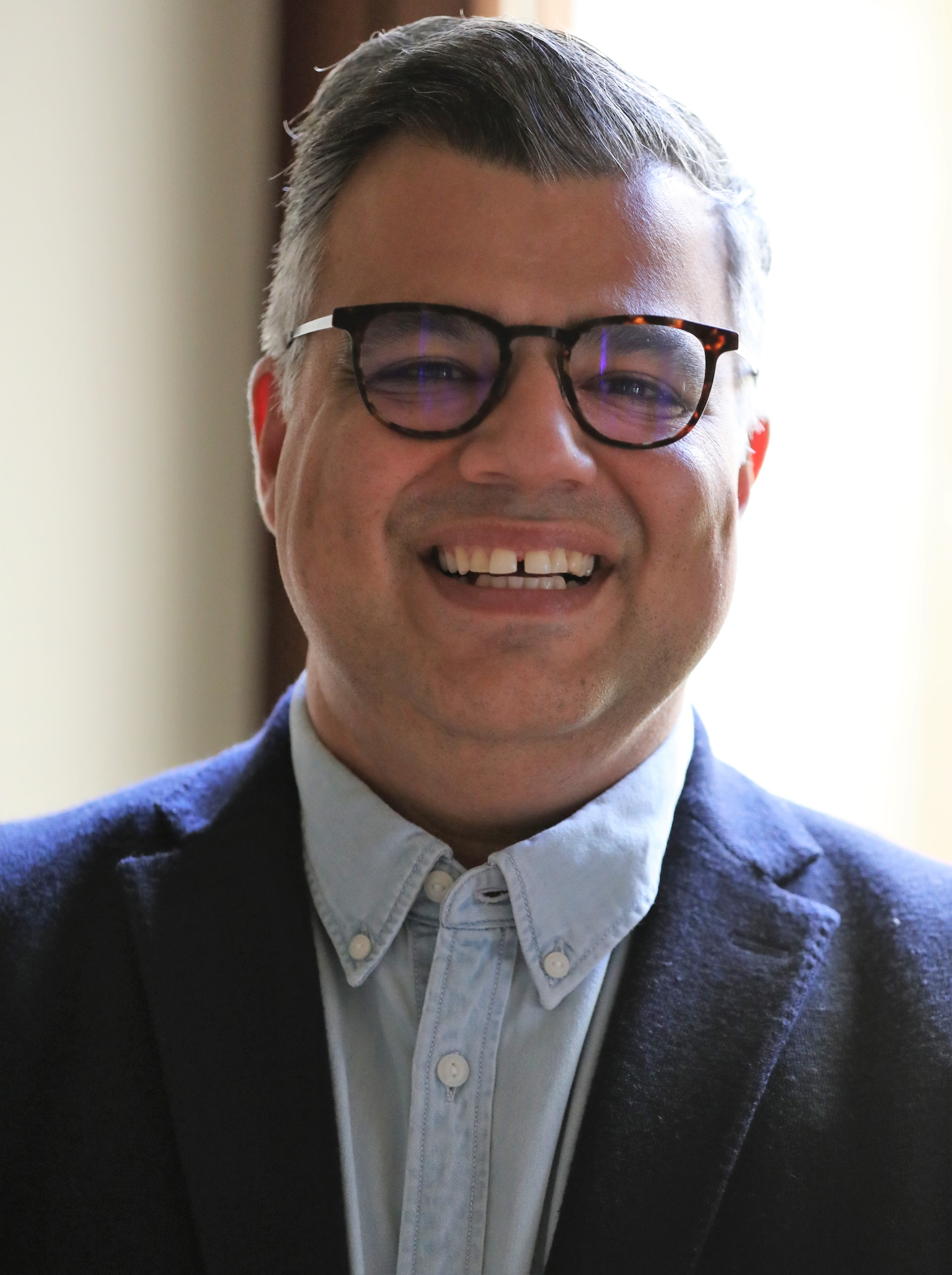 Ali Rezvan, a man wearing glasses and a suit and tie