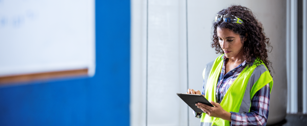 Female worker wearing neon vest and safety glasses using tablet.