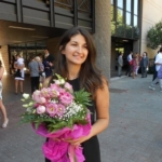 Krizia Ceccobao, a woman in a black dress with dark hair holding pink flowers outside a building.