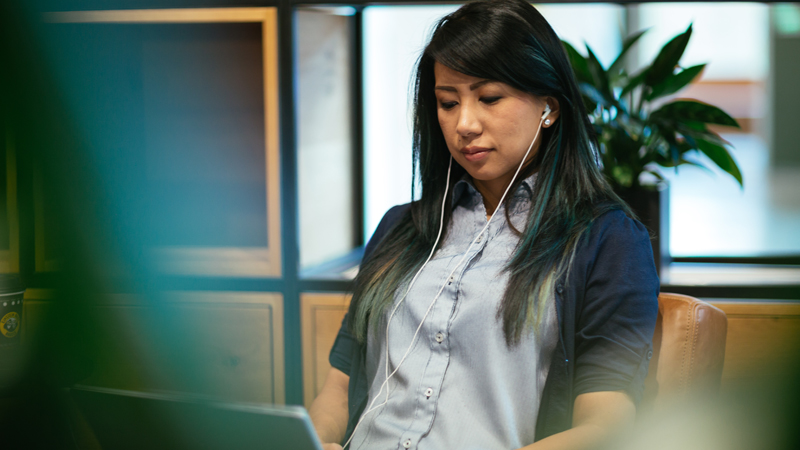 A woman works on her laptop with her headphones on.