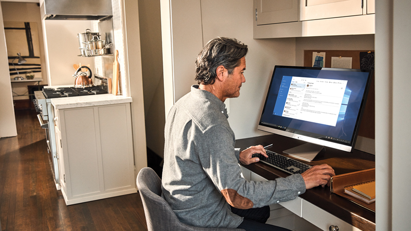 Photograph of a man working at a desktop computer from his home office area near his kitchen.