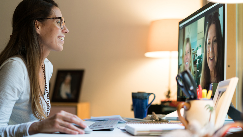 Woman using Skype video conferencing to conduct a work meeting.