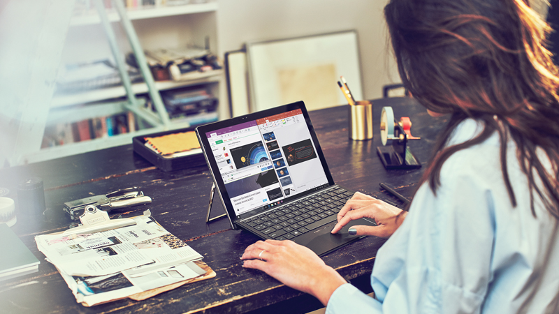 Woman working on a laptop seated at her desk in her home office. She has a clipboard, mail, and other supplies on her desk and a bookshelf in the background.