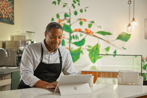 Photograph of a chef standing in a kitchen working on a Surface device
