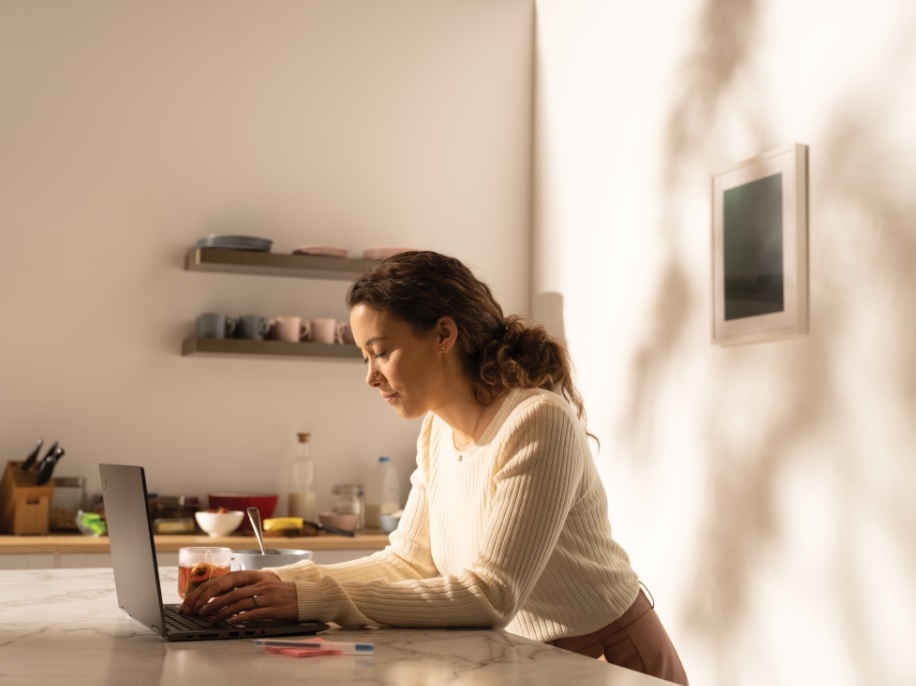 A woman getting started with her day in her kitchen and working on a Lenovo ThinkPad Yoga.