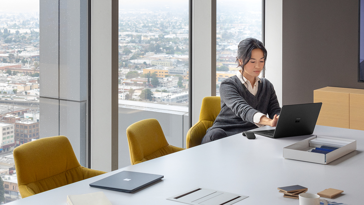 Woman working on her laptop in a conference room