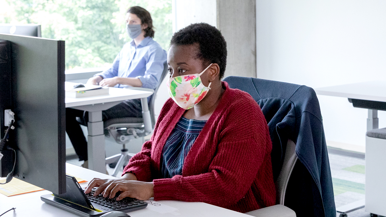 Woman wearing a mask, sitting at a desk and using a keyboard to type.