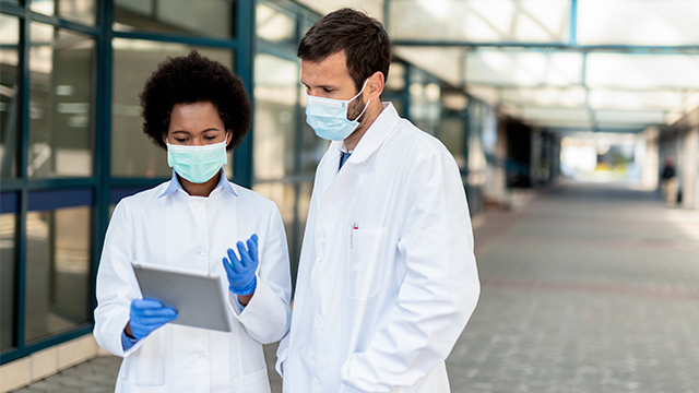 Doctors with face masks discussing something on the tablet.