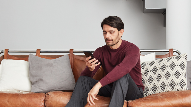 Man sitting on the couch looking down at the phone he is holding.