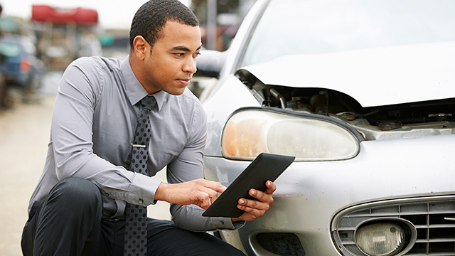 Car salesman crouching next to a car using a tablet