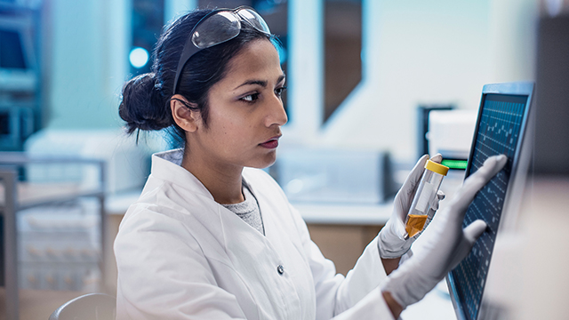 Woman in lab goggles and gloves working on a monitor.