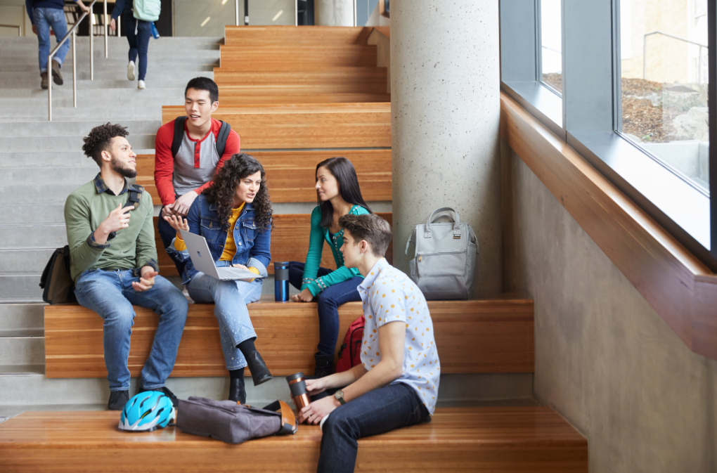 A group of male and female students seated together in an indoor common area on a university campus..