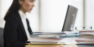 woman looking at a laptop with a pile a paperwork nearby