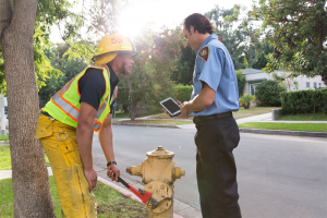 Firefighters looking a a tablet computer next to a hydrant.