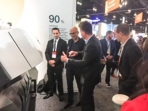 Microsoft CEO Satya Nadella gets a demo from Stuart Bashford, Chief Digital Officer from Bühler of LumoVision, showing the company's grain sorting technology that seeks out harmful toxins in grain to make food safer and reduce waste.