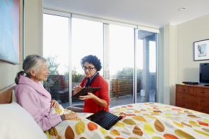A caregiver showing a tablet screen to an elderly patient lying in a bed