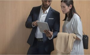 Man showing a woman something on a surface book.