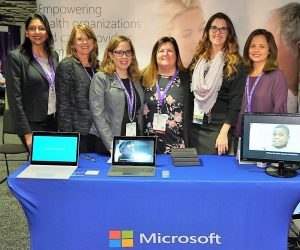 Six women standing behind a Microsoft table at a conference