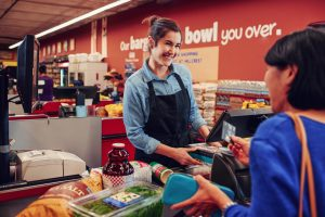Checkout clerk and customer transaction at a grocery store