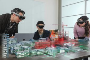 Three people building out a model of a city using virtual reality