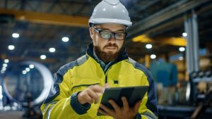 Factory employee in hardhat holding tablet