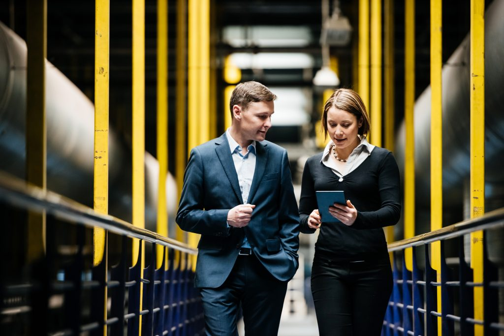 Two Business Person Walking A Dark Factory Hallway