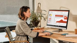 Woman looking at analytics on a desktop monitor