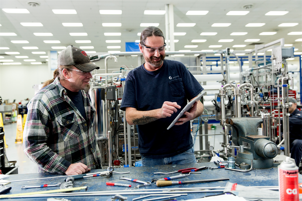 Two men working in factory while looking at device