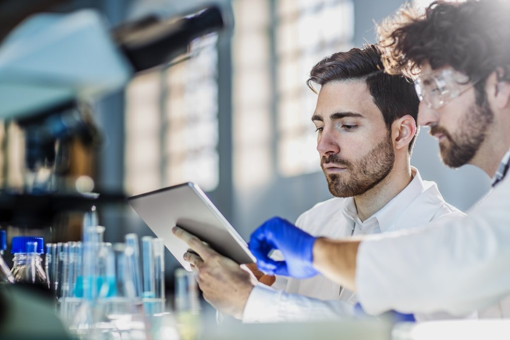 Two Scientists Using Digital Tablet In Laboratory