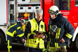 two firefighters analyze data on a Surface book