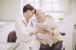 Senior woman at the doctor reviewing tablet