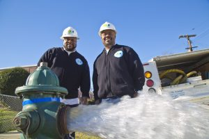 Two DC Water employees in front of fire hydrant