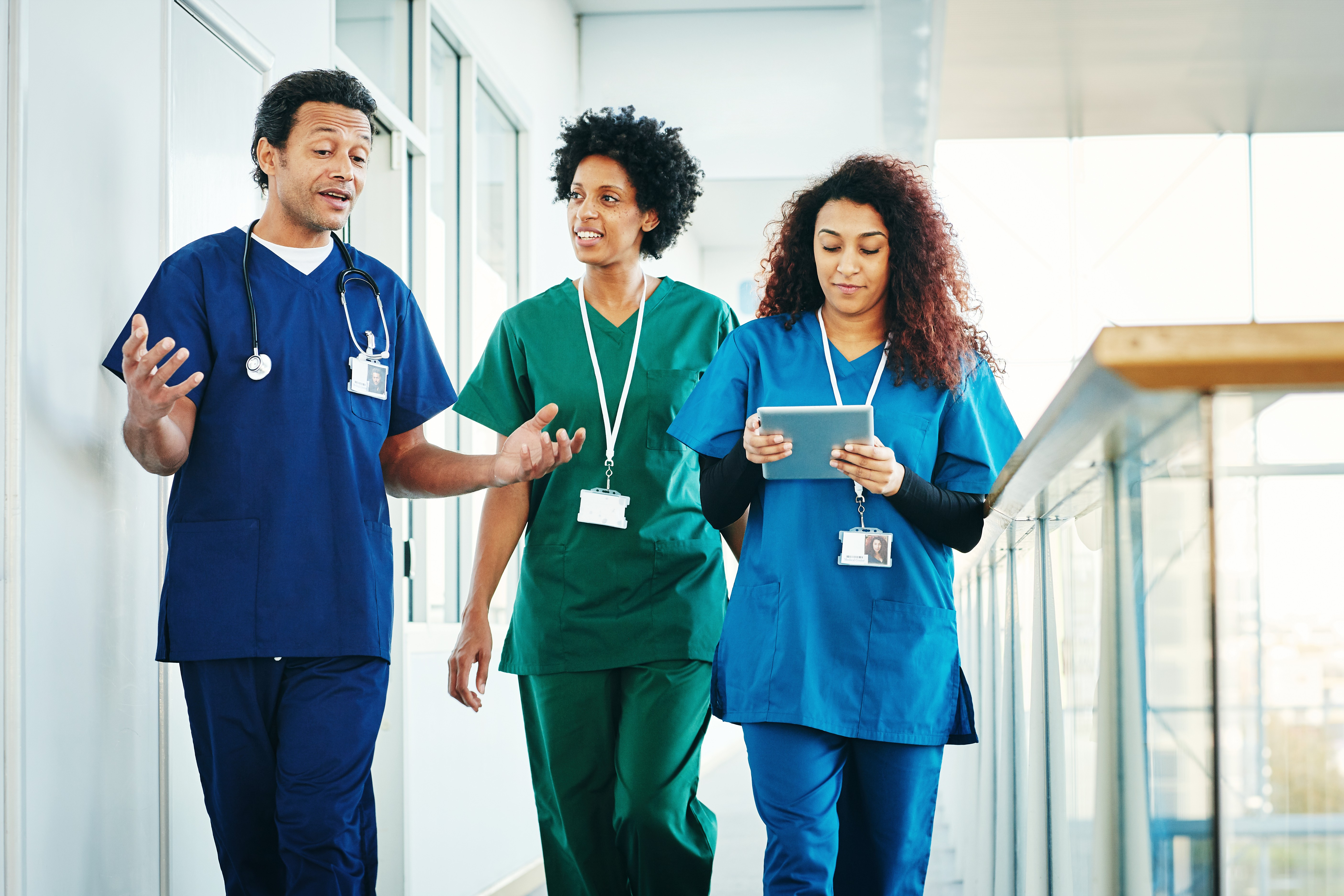 Group of medical professionals discussing while walking down hospital corridor