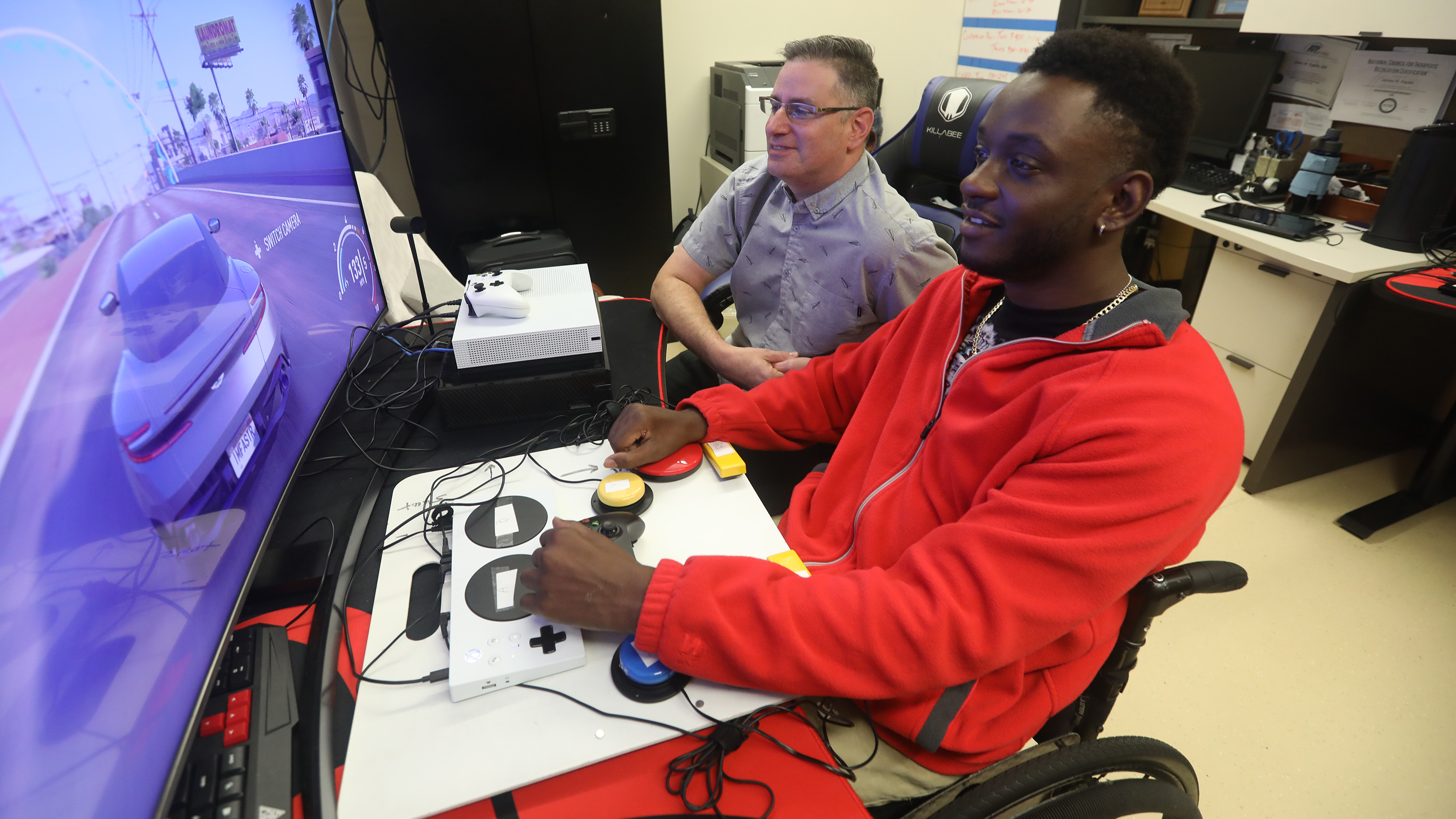 Man works with veteran with the XBOX Adaptive Controller