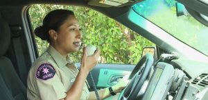 Police officer using radio in patrol car
