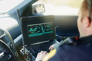 Police officer in a patrol car working on a computer