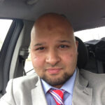 A headshot of Dr. Mufajjul Ali wearing a suit inside a car.