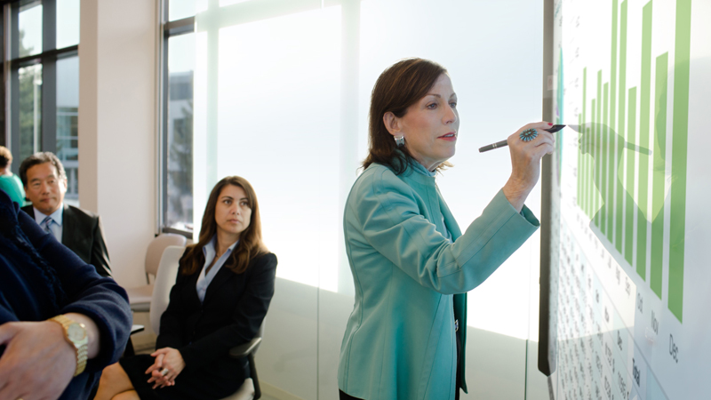 People in business attire going over numbers in a meeting using the Surface Hub.