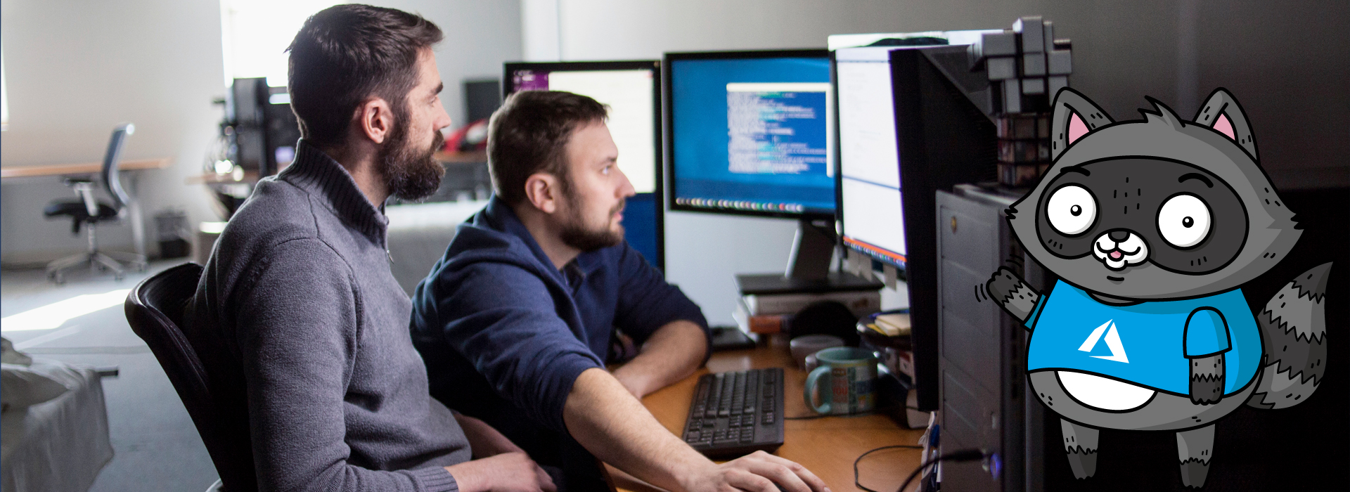 Two men working on a code project on a computer with multiple monitors. A picture of Bit the Raccoon is on the right of the image.