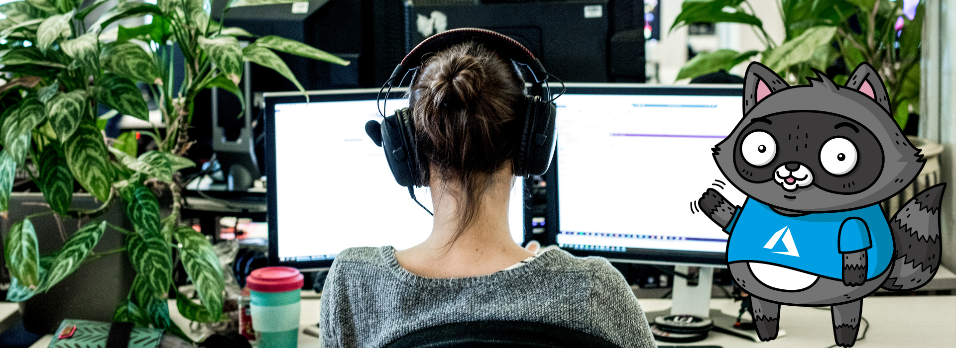 A woman sitting at a desk, working on a code project across two monitors. A picture of Bit the Raccoon is on the right of the image.