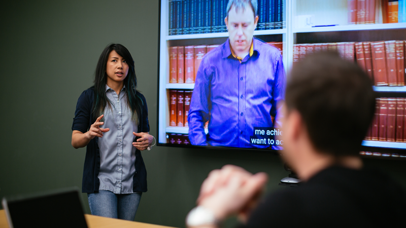 1. Photograph of Erika Martinez, a woman who is deaf, presenting using a screen with captions in a conference room.