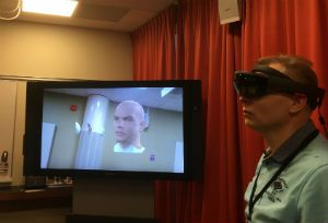 Man wearing the Microsoft Hololens and a tv screen behind him with a graphic of a human head on the screen